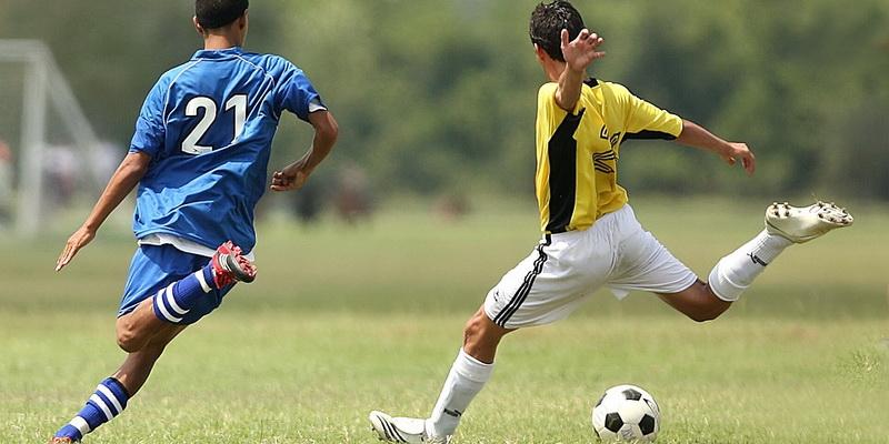 Du futbolo žaidėjai su kamuoliu