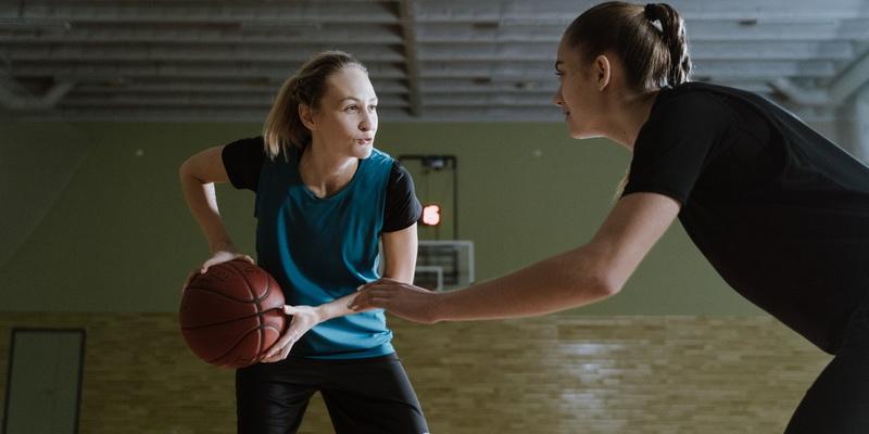 Dvi merginos žaidžia krepšinį